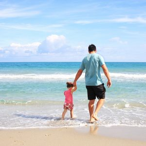 man holding childs hand at the beach