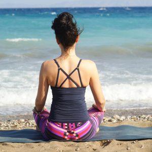 girl meditating at the beach