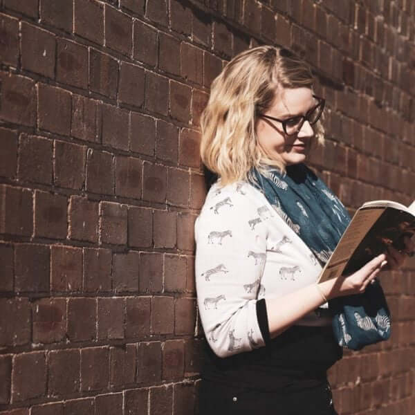 girl reading against a wall
